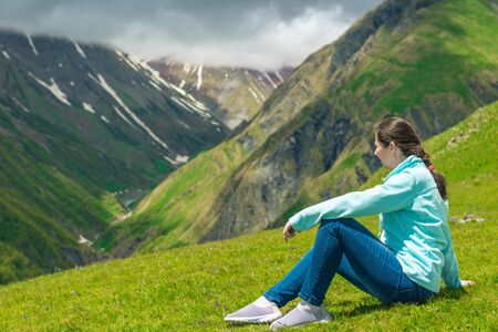 A woman sits on the grass and admires the beautiful mountain landscape in the Caucasus