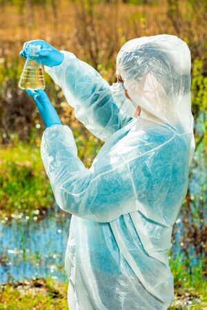 Vertical portrait of an environmentalist in protective clothing during work - lake water research