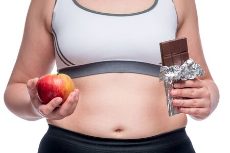Fat woman makes a difficult choice between an apple and chocolate, in the frame a close-up belly