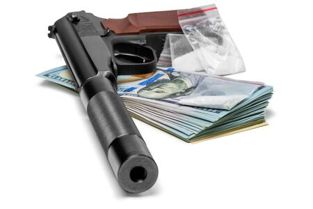 crime concept - a pistol with a silencer, money and drugs close up