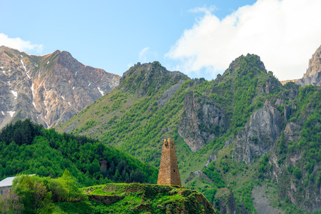 High traditional tower of Georgia on the background of high mountains of the Caucasus Editorial