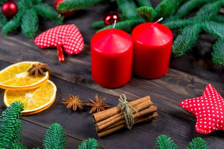 candles, spices and spruce branches Christmas objects on a wooden table, closeup