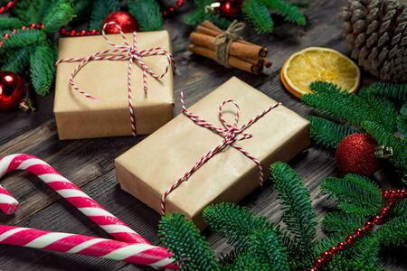 Two retro-style gifts with a red twine and candy cane surrounded by spruce branches close-up on dark boards