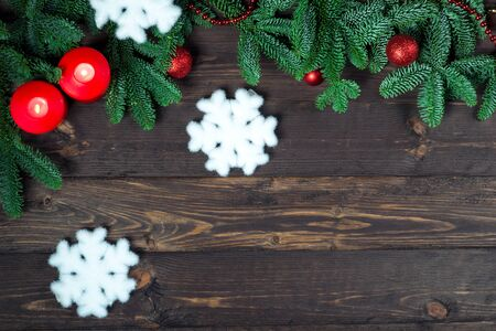 snowflakes and a pair of candles surrounded by fir branches on wooden boards, space for congratulations in the center of Merry Christmas Stockfoto