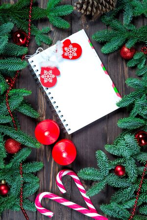 Notebook for writing greetings, New Year decorations and sweet candy cane top view greeting card closeup