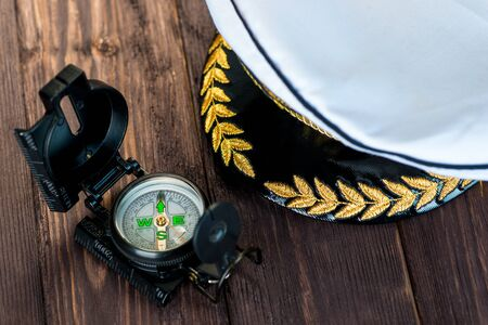 cap of the ship captain and next to it lies a compass on a wooden table