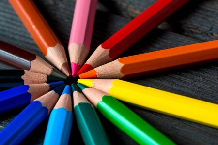 group of colored pencils arranged in a circle, close-up shot