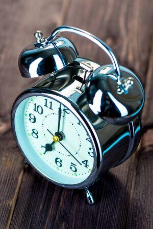 shiny steel alarm clock in retro style on wooden boards Stockfoto