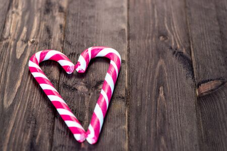 love concept, heart shaped candy cane on dark wooden background