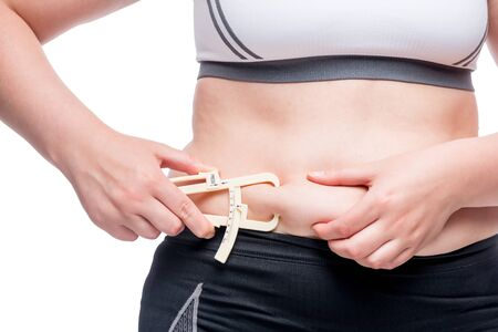 woman measures the level of fat on the abdomen with a tool isolated on white background