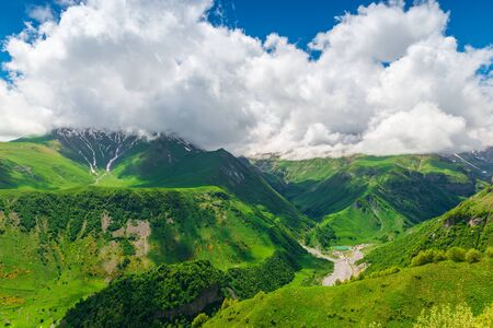 Beautiful cumulus clouds over the gorge and high mountains of the Caucasus in Georgia Stockfoto