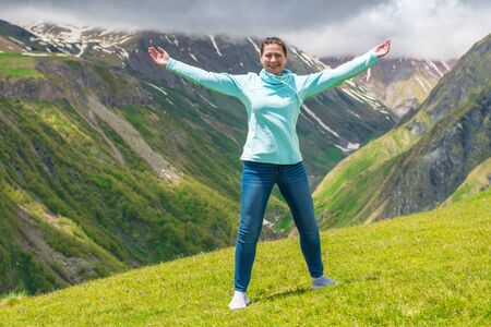 Portrait of a beautiful happy woman with arms outstretched in the mountains Stockfoto