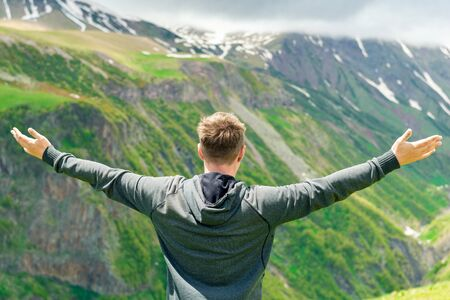 A man with his arms spread to the side enjoying the freedom and views of the mountains