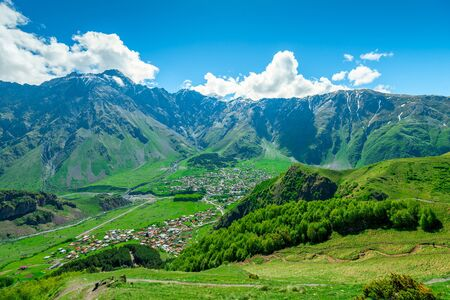 View of the mountain peaks of the Caucasus and the village of Gergeti in the valley, Georgia in summer Stockfoto