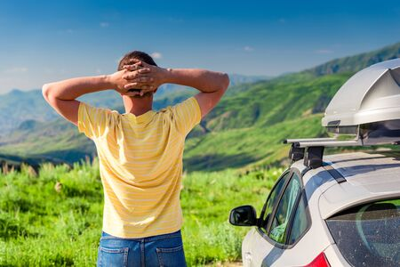 A road traveler stands next to a car and admires the beautiful mountains