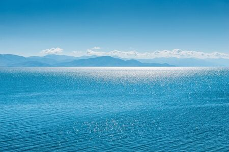 Lake Sevan in Armenia, sun glare on the water surface of the lake on a sunny day