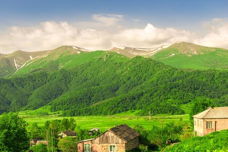 Mountain peaks covered with snow and green meadows on a sunny day in Armenia