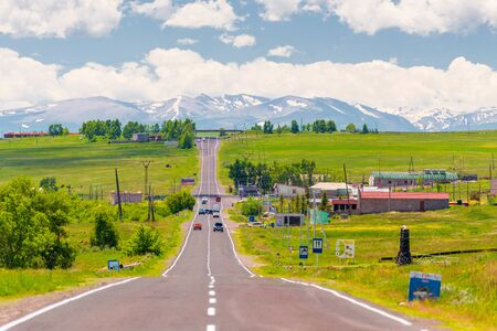 motorway through the village of Armenia overlooking the mountains with snowy peaks Stockfoto