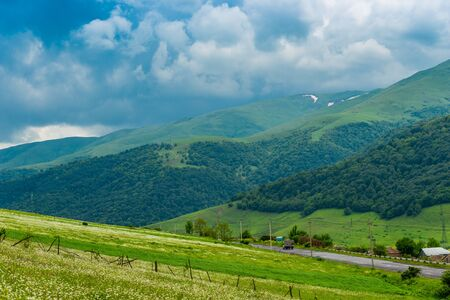 Blue clouds push by green picturesque mountains of the Caucasus, landscape of Armenia