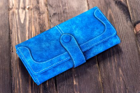 blue leather women wallet on wooden floor close-up 写真素材