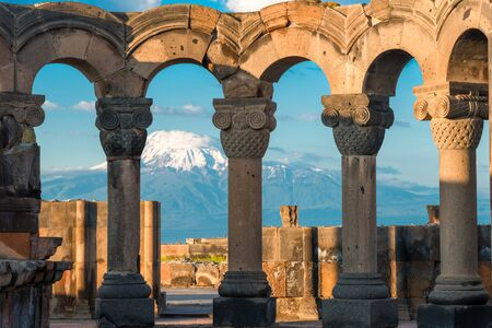 Columns of the ancient Zvartnots temple on the background of high snow-capped Mount Ararat, a tourist attraction Stock Photo