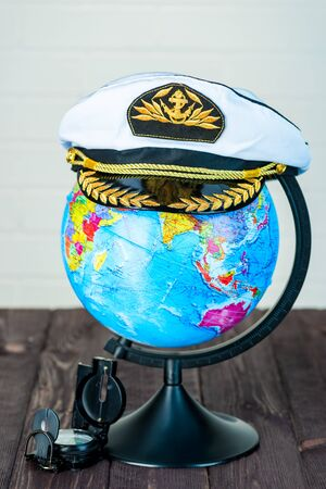 globe and compass, captain's cap, travel around the world concept
