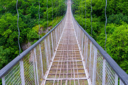 Swinging suspension bridge leading to the cave city of Khndzoresk over a gorge in the mountains of Armenia