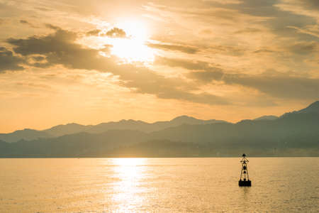 Lonely buoy lighthouse in the sea against the backdrop of picturesque mountains Stockfoto
