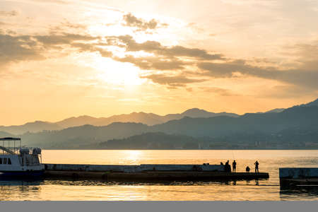Fishermen on a pier by the sea at sunset with fishing rods, beautiful landscape in Georgia
