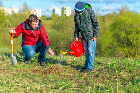 Father and son schoolboy in spring watering tree shoot in park concept family, help, togetherness