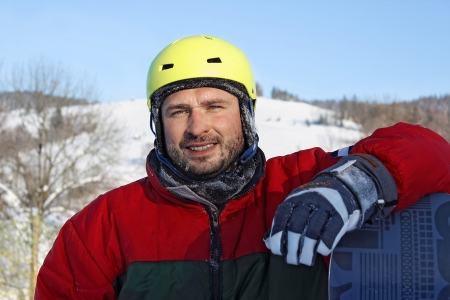 young man with snowboard clothes a helmet  in winter mountains photo