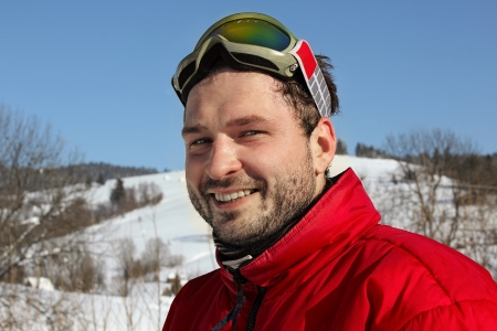 young man smiles in winter mountains with snowboard photo