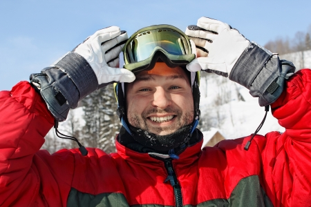 happy young man  lifting goggles  in winter mountians   photo