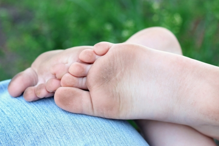 dirty feet: a little dirty feet of child are on the jeans in outdoor