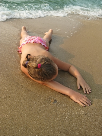 Adorable young girl lying on a sandy beach