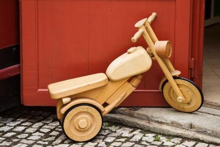 juguetes antiguos: bicicleta de juguete de madera se encuentra al lado de una puerta roja