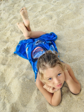 pretty young girl in blue dress lying on the beach, looking up photo