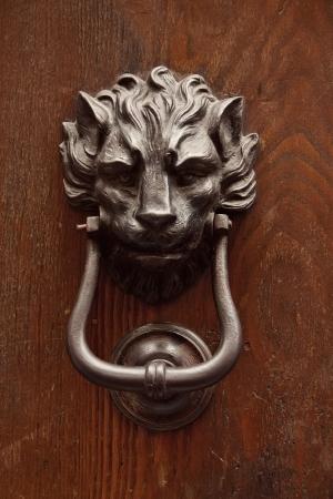 Antique knocker on a wooden door, Rome, Italy photo