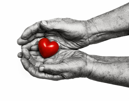 caring: elderly woman keeping red heart in her palms isolated on white background, symbol of care and love Stock Photo