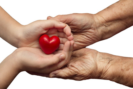 tiredness: little girl and elderly woman keeping red heart in their palms together, isolated on white , symbol of care and love