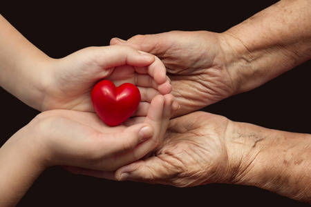 little girl and elderly woman keeping red heart in their palms together, symbol of care and love Stock Photo - 26036801