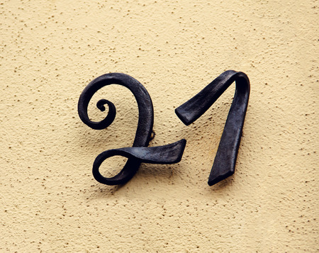 cast metal type: Metal house number twenty-one  Separate black lettering on a wall