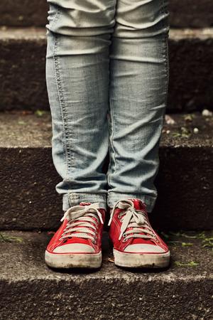 first step: Kleines M�dchen in roten Turnschuhen und Jeans, die auf der Treppe machen ersten Schritt Lizenzfreie Bilder