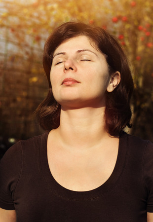 Close up portrait of beautiful woman is smiling with closed eyes over sunlight, meditation outdoor