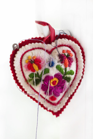 stitchwork: Embroidered pincushion in form heart with needles, handmade Stock Photo