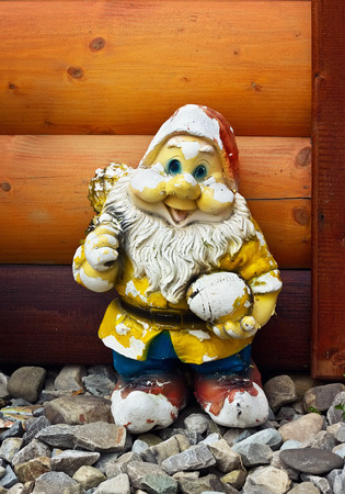 Shabby Old Figure Of A Garden Gnome Against The Wooden Planking Background  Outdoors Stock Photo