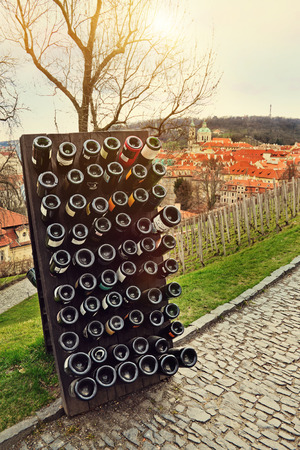 Collection sparkling wines aging in the rack outdoors against old town Prague, Czech Republic photo