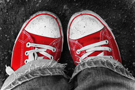 first step: Feet in schmutzigen roten Turnschuhen und Jeans im Freien. Macht ersten Schritt.