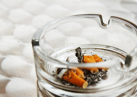 imminence: Cigarette butts in a glass ashtray, smoking in public places