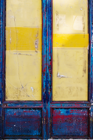squalid: Old grungy wooden door with peeling paint and broken glass